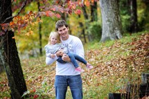 Father cradling young daughter outdoors