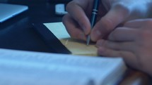 A young man's hand is writing notes from a Bible study.