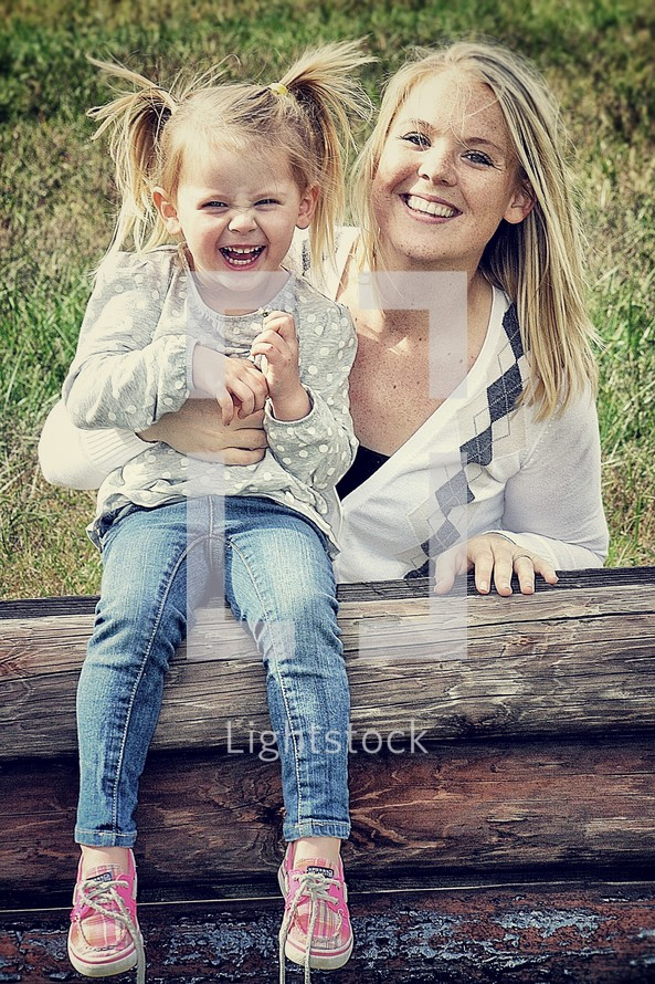 Mother and young daughter smiling