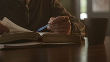 a man reading a Bible during his morning Bible study and taking notes.
