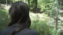 a woman looking into a forest