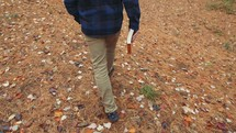 a man carrying a Bible walking into the woods in fall