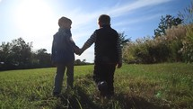 boys walking holding hands in a field outdoors