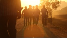 men walking down a dirt road at sunset