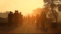 walking down a dirt road in India at sunset