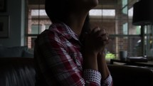 Woman sitting in a home praying.