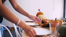 woman setting a table for Thanksgiving dinner