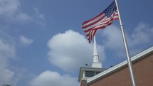 church steeple and American flag on a flag pole