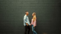 a couple talking in front of a gray background