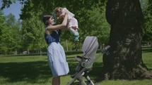 a mother lifting her daughter out of a stroller