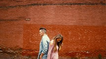a couple standing back to back in front of a brick building