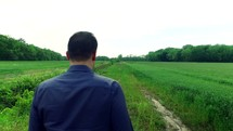 man walking on a path through a field outdoors