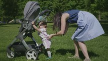 a mother and toddler girl pushing a stroller through the grass