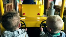 children riding on a yellow train ride