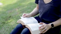 young woman sitting on a hill reading a Bible