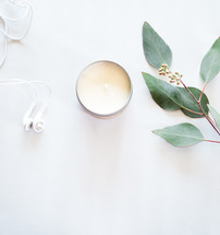 White earphones, candle and green leaves on a white surface.