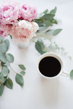 A vase of pink peonies and a cup of coffee on a white surface.