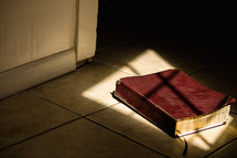 a Bible lying in sunlight on the floor