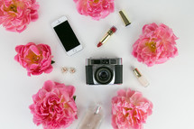 pink flowers, camera, lipstick, perfume, cellphone, earrings on white background