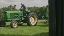 a farmer getting off of a tractor