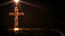 Jesus Christ on cross with golden light on black background with defocused lights spinning around. Easter background. Seamless looping 4k