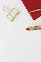 gold clip, red planner, red lipstick, and gold pen