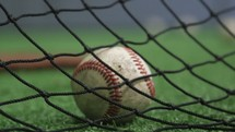 baseballs on a field by netting