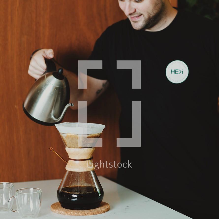 man slow brewing coffee