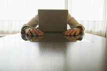 Caucasian businessman hiding behind laptop