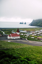 ref roof church and homes along a shore in a town in Iceland