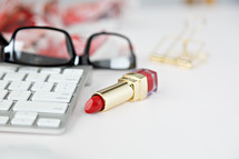 reading glasses, computer keyboard, red lipstick, floral scarf