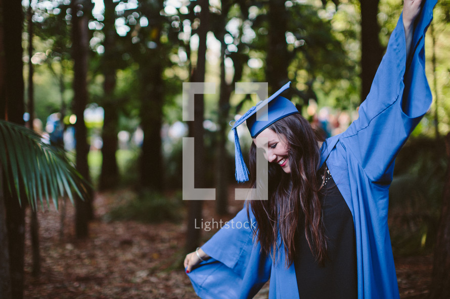Woman in a graduation gown and hat, celebrating