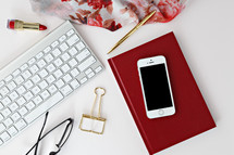 red lipstick, reading glasses, clip, computer keyboard, phone, scarf, pen, and red book on a desk