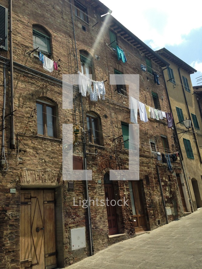 clothes on clotheslines hanging from a brick building in Italy