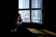 woman sitting on a floor next to a window in a city