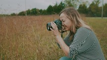 a woman taking a picture in a field