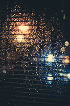 blinds and rain drops on a window at night