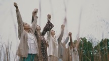 women walking through a field of tall grasses with raised hands