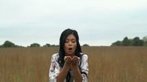a woman blowing confetti
