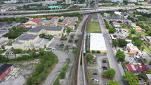 Aerial View of Train Pulling Out Of Station Into Downtown City