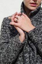model's hands over her sweater