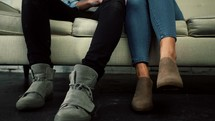 legs of a couple sitting on a couch