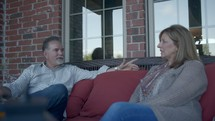 a man and a woman talking on a porch
