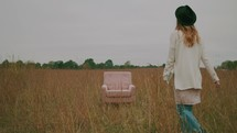 a woman walking through a field of tall grasses to sit in a chair