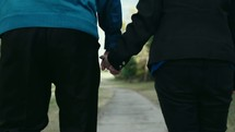 an elderly couple walking holding hands