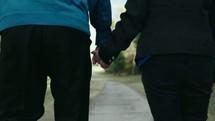 an elderly couple walking holding hands