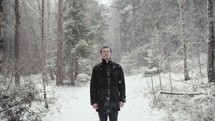 a man standing in a forest in falling snow