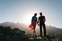 Silhouette of a man and woman, standing on a rocky hilltop, mountains in the background