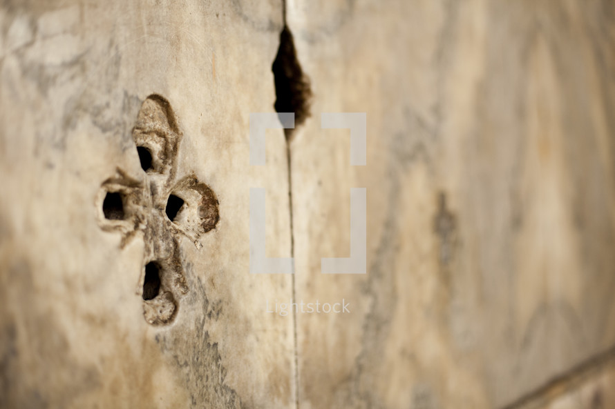 A cross carved onto a piece of wood