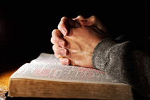 A man's hands clasped in deep prayer over a Holy Bible.